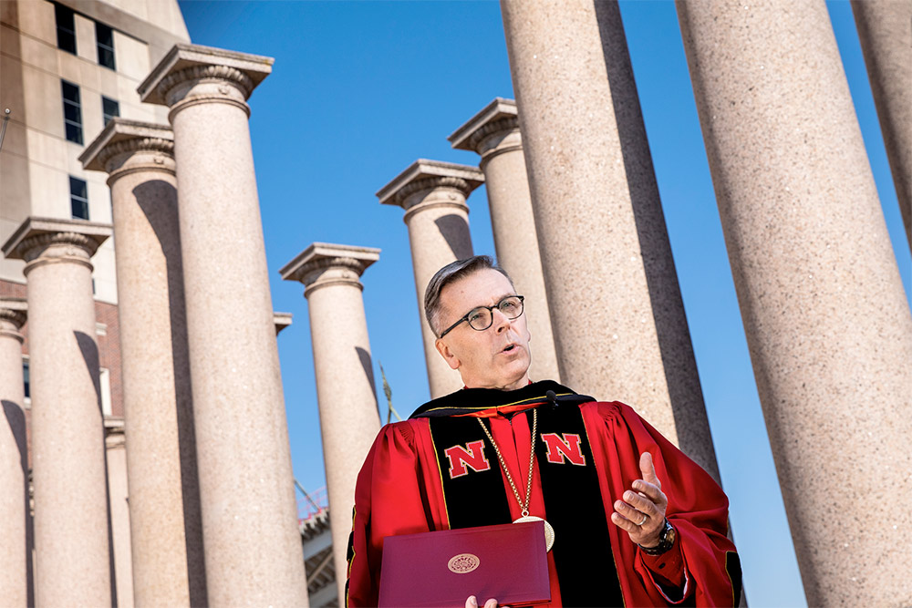 Ronnie Green conferring degrees in front of columns