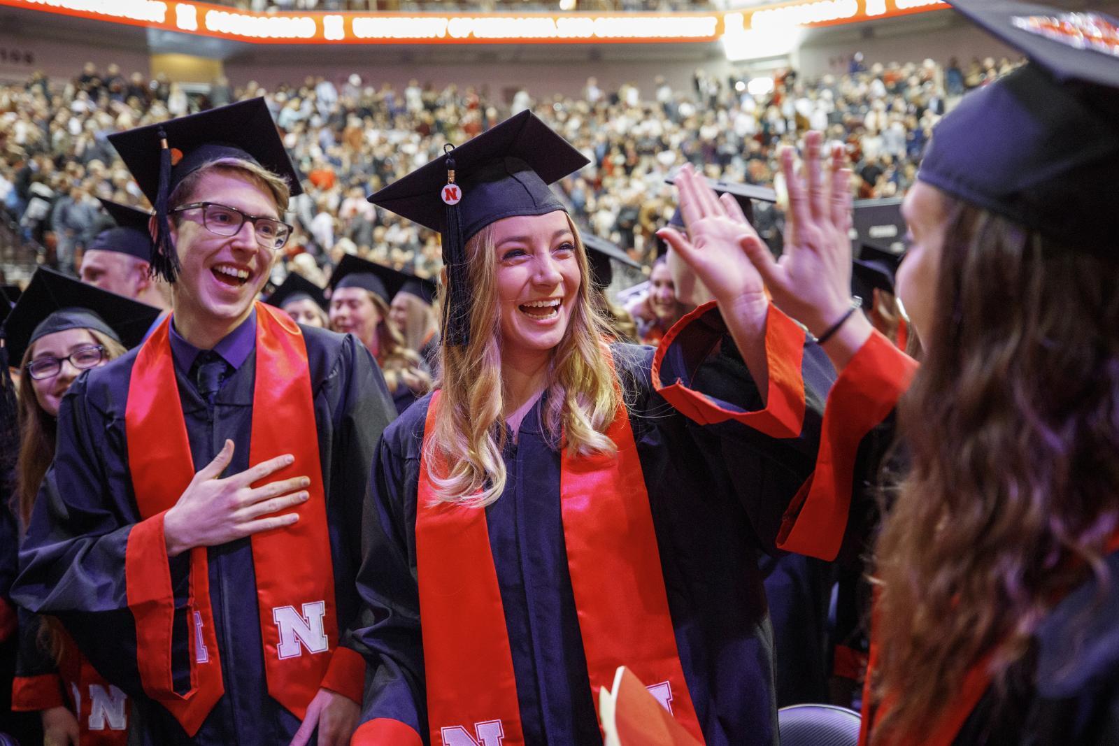 Nebraska graduates high five after receiving their diplomas.