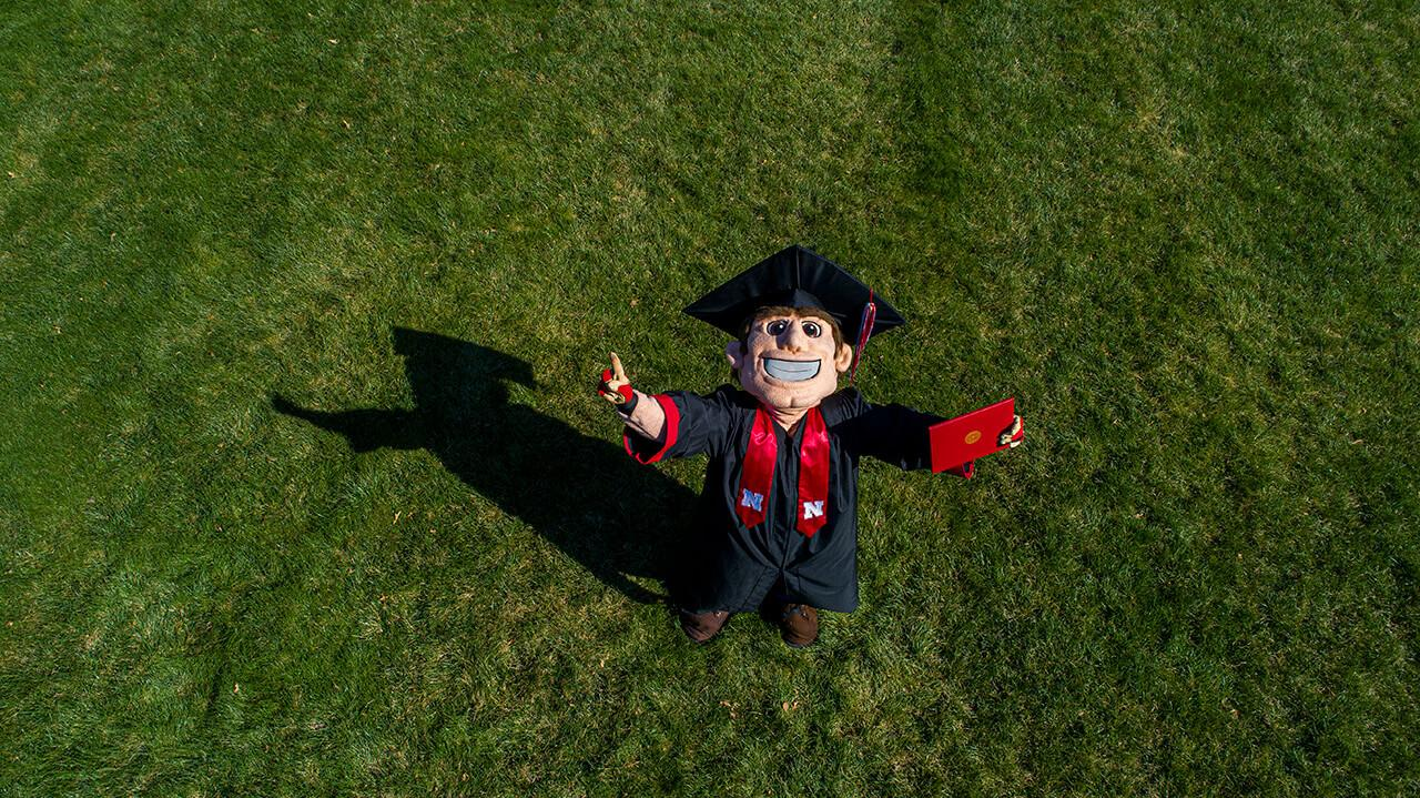 Image from above of Herbie Husker in graduation mortar and robe with arms upraised on grassy lawn.