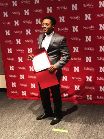 Student posing with award in front of red background