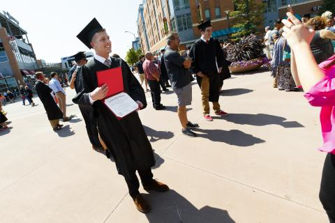 New graduate with his diploma outside Pinnacle Bank Arena