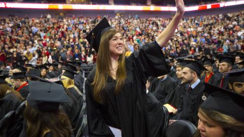 Graduate waving at commencement