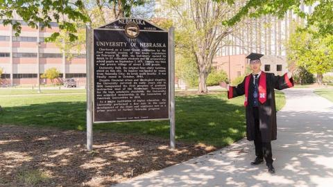 Graduate standing by sign about Nebraska