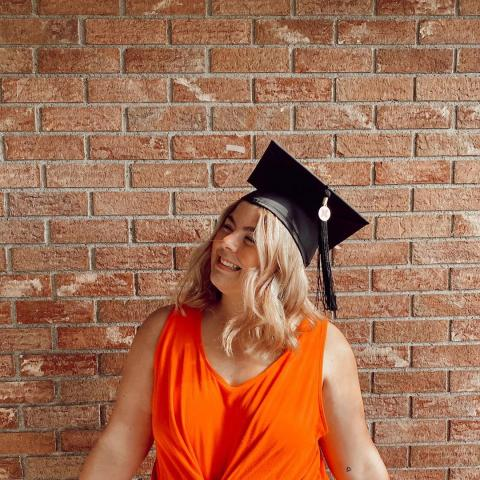 Graduate in orange dress wearing mortar cap.