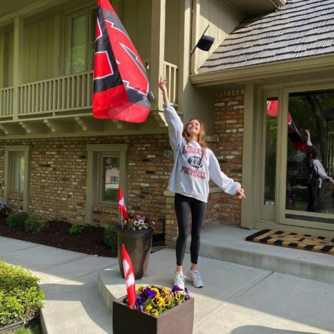Student celebrating at home with Husker flag