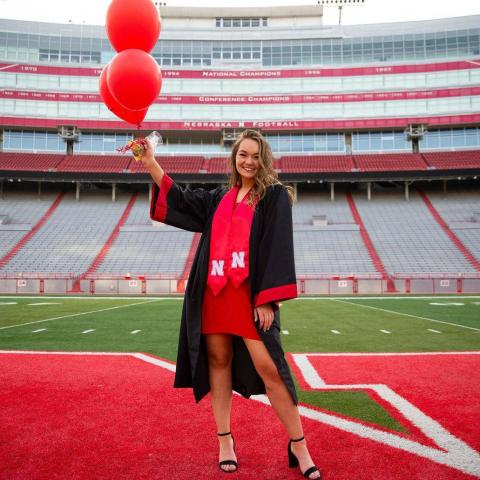Graduate posing with balloons and robe in Memorial Stadium