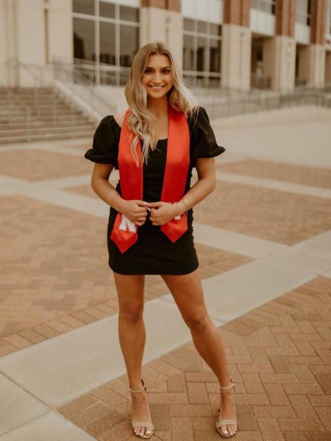 Graduate posing outside with red sash