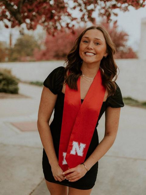Student smiling outside with red sash