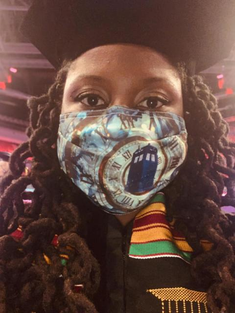 Graduate selfie with cap and mask inside