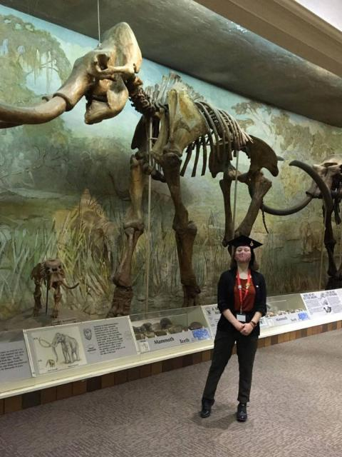 Graduate posing in front of skeleton at Morrill Hall