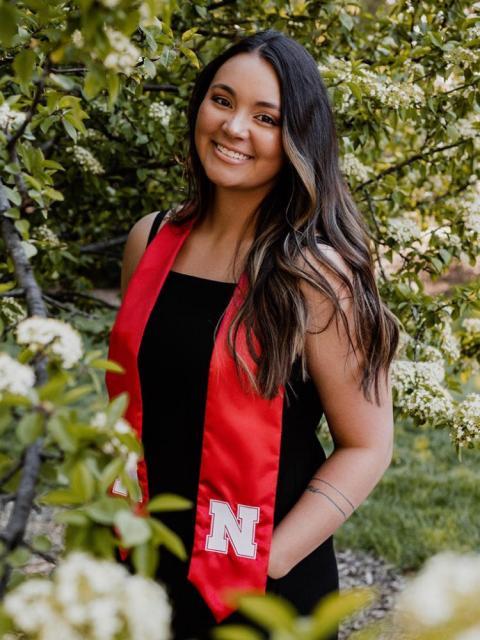 Graduate portrait outside by trees