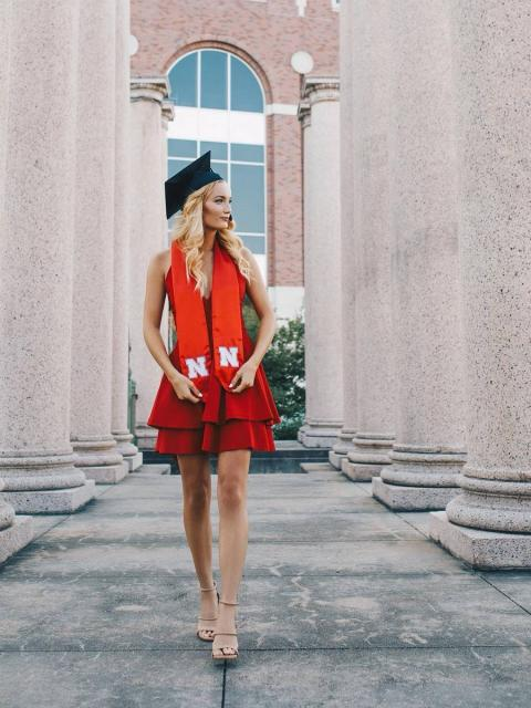 Graduate standing by columns wearing red